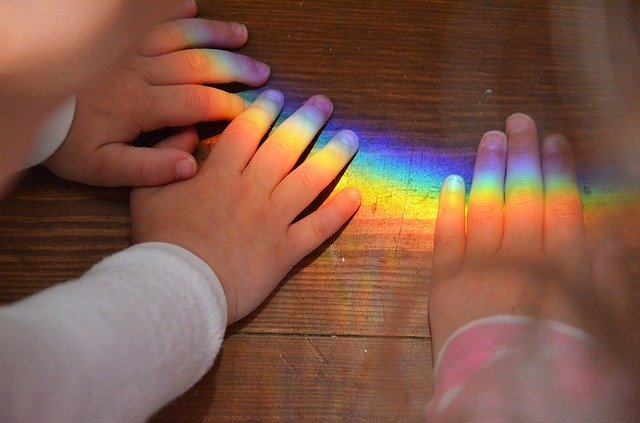 kids hands and rainbow